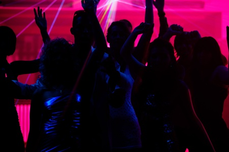 Photo for Silhouettes of dancing people having a celebration in a disco club, the light show is sending laser beams through the backlit scene - Royalty Free Image