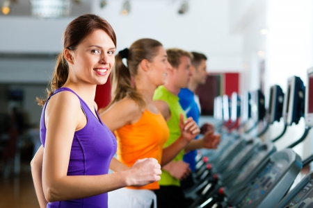 Running on treadmill in gym or fitness club - group of women and men exercising to gain more fitness