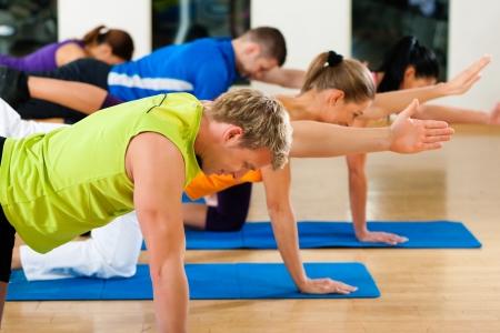Foto per Group of five people is doing stretching exercises in fitness club on gym mats - Immagine Royalty Free