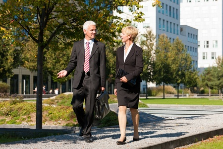 Business people - mature or senior -  talking outdoors and walking in a park