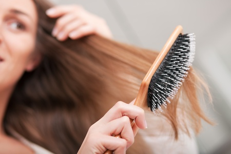 Photo pour Young woman brushing her long dark-blond hair after getting up in the morning; focus on brush!  - image libre de droit