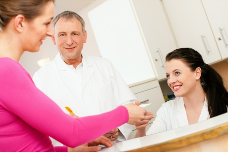 Photo for Patient in reception area of office of doctor or dentist, handing her health insurance card over the counter to the nurse, the doctor standing in the background and is writing things on a clipboard  - Royalty Free Image