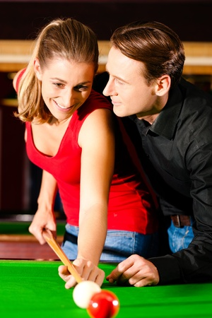 Couple  man and woman  in a billiard hall playing snooker