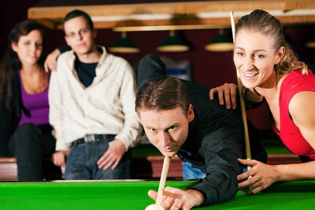 Group of four friends in a billiard hall playing snooker