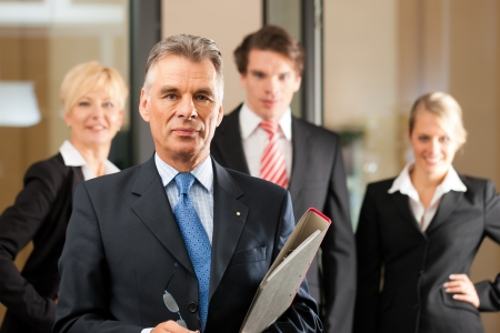Photo for Business - team in an office, the senior manager is standing in front - Royalty Free Image