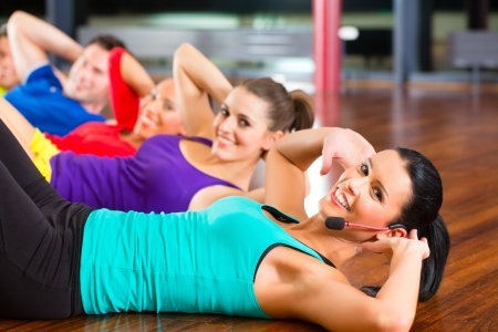 Photo for Fitness group with instructor in gym doing stomach crunches for sport - Royalty Free Image