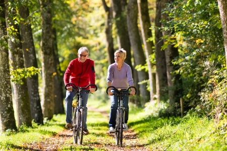 Photo for Senior Man and woman exercising with bicycles outdoors, they are a couple - Royalty Free Image