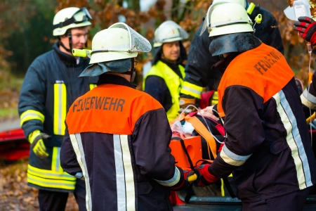Foto de Accident - Fire brigade and Rescue team pulling cart with wounded person wearing a neck brace and respirator - Imagen libre de derechos