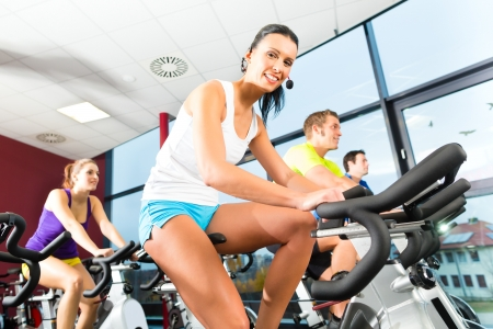 Photo pour Young People - group of women and men - doing sport Spinning in the gym for fitness - image libre de droit