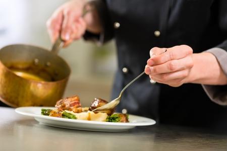 Foto de Chef in hotel or restaurant kitchen cooking, only hands to be seen, he is working on the sauce for the food as saucier - Imagen libre de derechos