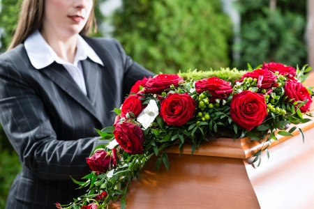Photo for Mourning woman on funeral with red rose standing at casket or coffin - Royalty Free Image