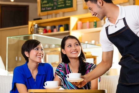 Foto de Asian female friends enjoying her leisure time in a cafe, drinking cappuccino and talking about some things, a Indonesian waiter serving the coffee - Imagen libre de derechos