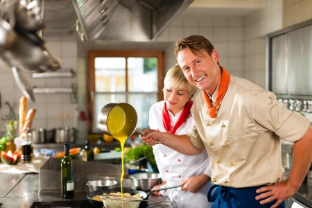 Photo for Two chefs in teamwork - man and woman - in a restaurant or hotel kitchen cooking delicious food - Royalty Free Image