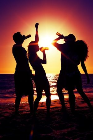 People (two couples) on the beach having a party, drinking and having a lot of fun in the sunset (only silhouette of people to be seen, people having bottles in their hands with the sun shining through)