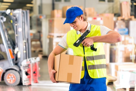 Photo pour Warehouseman with protective vest and scanner, scans bar-code of package, he standing at warehouse of freight forwarding company - image libre de droit