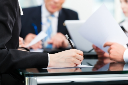 Foto de Business - meeting in an office, lawyers or attorneys discussing a document or contract agreement - Imagen libre de derechos