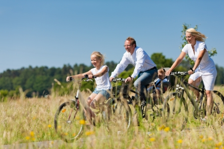 Foto de Family with baby and and daughter having a weekend excursion on their bikes on a summer day in beautiful landscape - Imagen libre de derechos