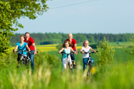 Foto de Family with three girls having a weekend excursion on their bikes on a summer day in beautiful landscape - Imagen libre de derechos
