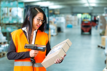 Photo pour Logistics - female worker or shipper with protective vest and scanner, scans bar-code of package, he standing at warehouse of freight forwarding company - image libre de droit