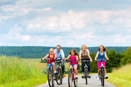 Photo for Family with three girls having a weekend excursion on their bikes on a summer day in beautiful landscape - Royalty Free Image