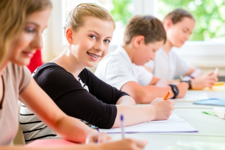 Photo for Students or pupils of school class writing an exam test in classroom concentrating on their work - Royalty Free Image