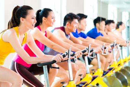 Foto de Chinese Asian sport group of men and women in fitness club or gym exercising on spinning bikes - Imagen libre de derechos