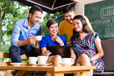 Photo for Asian friends or colleagues enjoying leisure time in a cafe, drinking coffee or cappuccino and looking at photos or emails on a tablet computer - Royalty Free Image