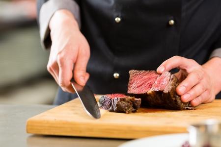 Foto de Chef in hotel or restaurant kitchen cooking, only hands, he is cutting meat or steak - Imagen libre de derechos