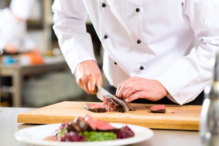 Foto de Chef in hotel or restaurant kitchen cooking, only hands, he is cutting meat or steak for a dish on plate - Imagen libre de derechos