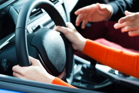 Foto de Driving School - Young woman steer a car with the steering wheel, maybe she has a driving test perhaps she exercises the parking - Imagen libre de derechos