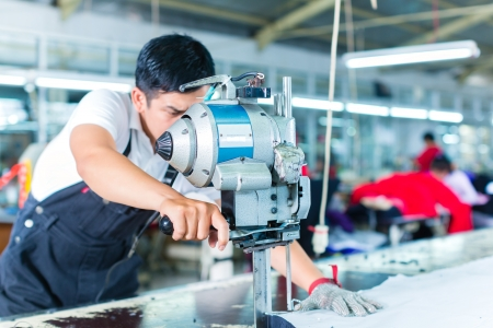 Photo for Indonesian worker using a cutter - a large machine for cutting fabrics - in a asian textile factory, he wears a chain glove - Royalty Free Image
