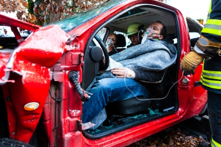 Foto de victim in a crashed vehicle, she receives first aid from firefighters - Imagen libre de derechos