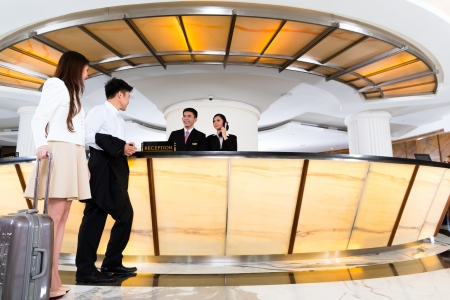 Photo for Asian Chinese woman and man arriving at front desk or reception of luxury hotel in business clothes with trolley  - Royalty Free Image