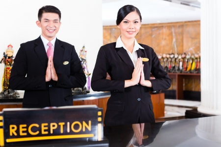 Photo for Chinese Asian reception team at luxury hotel front desk welcoming guests with typical gesture, a sign of good service and hospitality - Royalty Free Image