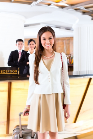 Photo for Asian Chinese woman arriving at front desk of luxury hotel in business clothes with trolley - Royalty Free Image