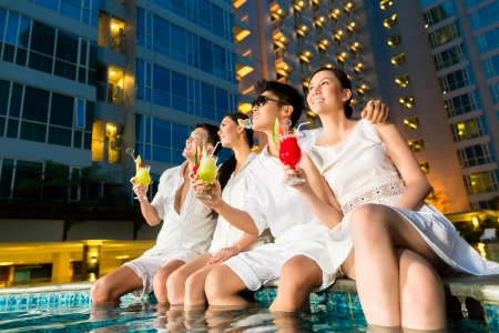 Photo pour Two young and handsome Asian Chinese couples or friends drinking cocktails in a luxurious and fancy hotel pool bar  - image libre de droit