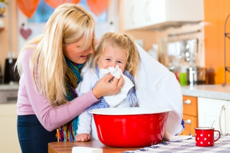 Foto de Mother care for sick child with vapor-bath at domestic kitchen  - Imagen libre de derechos
