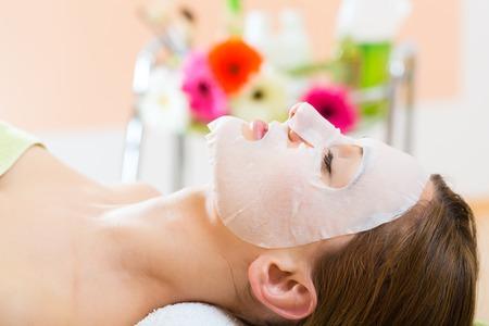 Foto de Wellness - woman receiving facial mask in spa for clean skin - Imagen libre de derechos