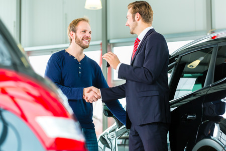 Photo pour Seller or car salesman and customer in auto dealership, they shaking hands, hands over the car keys and seal the purchase of the auto or new car - image libre de droit