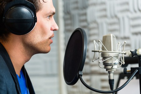Photo for Young male singer or musician with microphone and headphone for audio recording in the Studio - Royalty Free Image