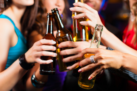 Foto de Group of party people - men and women - drinking beer in a pub or bar - Imagen libre de derechos