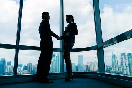 Photo for Asian business people handshake to seal deal in front of city skyline - Royalty Free Image