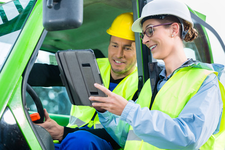 Photo for Construction worker in construction machinery discussing with engineer blueprints on pad or tablet computer on site - Royalty Free Image