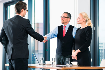 Photo for Business - young man in job interview for hiring, welcomes, Boss or Senior and his female Assistant in their office - Royalty Free Image