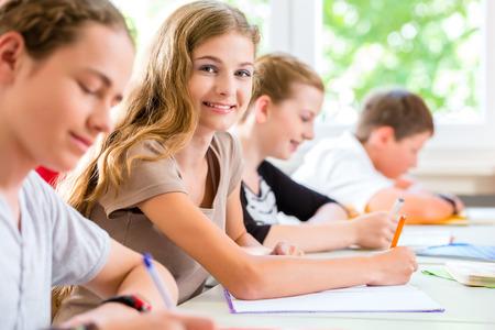 Foto de Students or pupils of school class writing an exam test in classroom concentrating on their work - Imagen libre de derechos