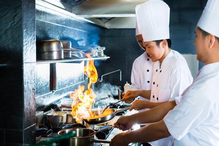 Photo pour Side view of chefs cooking together - image libre de droit