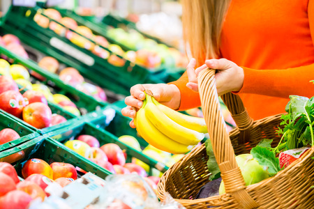 Photo pour Woman in supermarket at the fruit shelf shopping for groceries, she is putting a banana in her basket - image libre de droit
