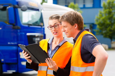 Photo pour Logistics - proud driver or forwarder and female coworker with tablet computer, in front of trucks and trailers, on a transshipment point, its a good and successful team - image libre de droit