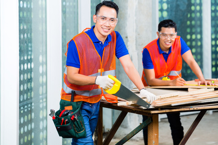 Foto de Asian Indonesian builder or craftsman sawing with a saw a wood board of a tower building or construction site wearing protection glasses and gloves - Imagen libre de derechos