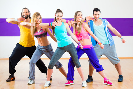 Photo for Group of men and women dancing zumba fitness choreography in dance school - Royalty Free Image